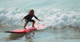 Kind mit Neoprenanzug surft
