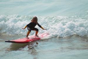 Kind mit Kinder Neoprenanzug beim Surfen